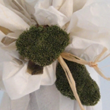 Jar wrapped in handmade paper decorated with raffia and dried moss