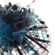 Round box wrapped in foil paper with feather and bow decoration