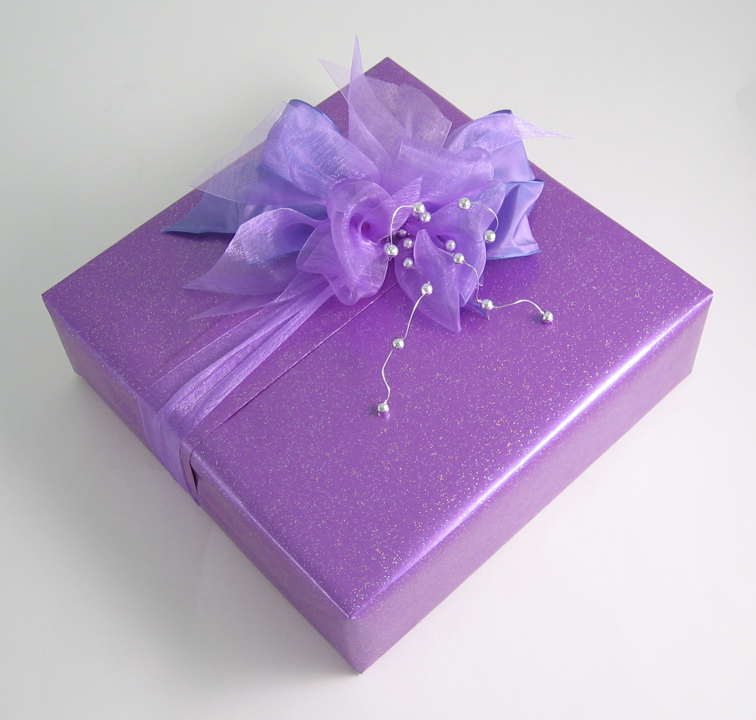 A wrapped box decorated with a fabric ribbon bow