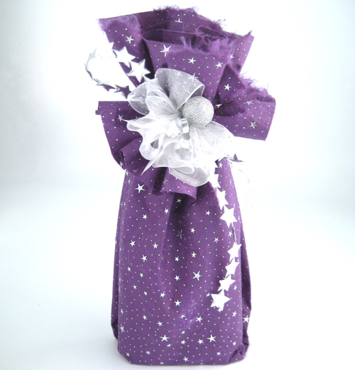 Gift wrapped in handmade paper, decorated with assorted ribbons and a bauble